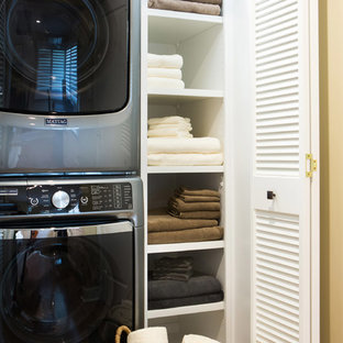 Laundry closet - small transitional single-wall medium tone wood floor laundry closet idea in Los Angeles with open cabinets, white cabinets, white walls and a stacked washer/dryer