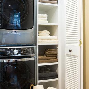 Klassisk inredning av en liten linjär liten tvättstuga, med öppna hyllor, vita skåp, vita väggar, mellanmörkt trägolv och en tvättpelare