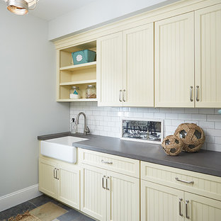 Example of a mid-sized beach style galley slate floor dedicated laundry room design in Grand Rapids with a farmhouse sink, shaker cabinets, concrete countertops, a side-by-side washer/dryer, beige cabinets and gray walls