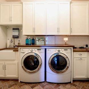 Idéer för små vintage l-formade brunt tvättstugor enbart för tvätt, med en rustik diskho, släta luckor, vita skåp, träbänkskiva, vitt stänkskydd, stänkskydd i keramik, vita väggar, klinkergolv i porslin, en tvättmaskin och torktumlare bredvid varandra och brunt golv