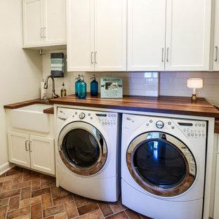 Exempel på en liten klassisk bruna l-formad brunt tvättstuga enbart för tvätt, med en rustik diskho, släta luckor, vita skåp, träbänkskiva, vitt stänkskydd, stänkskydd i keramik, vita väggar, klinkergolv i porslin, en tvättmaskin och torktumlare bredvid varandra och brunt golv