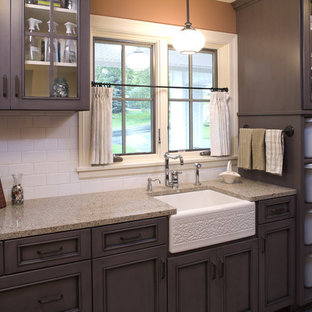 This is an example of a mid-sized traditional galley utility room in Minneapolis with a farmhouse sink, glass-front cabinets, granite benchtops and beige benchtop.