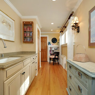 Inspiration for a large country galley utility room in New York with an undermount sink, raised-panel cabinets, beige cabinets, granite benchtops, beige walls, medium hardwood floors, a side-by-side washer and dryer, brown floor, grey splashback and planked wall panelling.