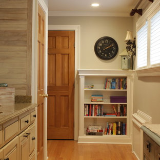 This is an example of a large country single-wall utility room in New York with an undermount sink, raised-panel cabinets, beige cabinets, granite benchtops, grey walls, medium hardwood floors, a side-by-side washer and dryer, brown floor, grey splashback, multi-coloured benchtop and planked wall panelling.
