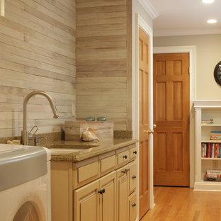 Idéer för ett stort lantligt flerfärgad linjärt grovkök, med en undermonterad diskho, luckor med upphöjd panel, beige skåp, granitbänkskiva, grå väggar, mellanmörkt trägolv, en tvättmaskin och torktumlare bredvid varandra, brunt golv och grått stänkskydd