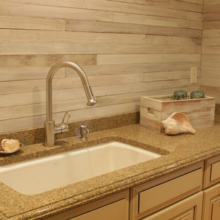 Photo of a large country single-wall utility room in New York with an undermount sink, raised-panel cabinets, beige cabinets, granite benchtops, grey walls, medium hardwood floors, a side-by-side washer and dryer, brown floor, grey splashback, multi-coloured benchtop and planked wall panelling.
