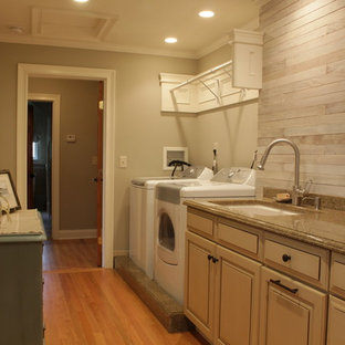 Large country single-wall utility room in New York with an undermount sink, raised-panel cabinets, beige cabinets, granite benchtops, grey walls, medium hardwood floors, a side-by-side washer and dryer, brown floor, grey splashback, timber splashback and planked wall panelling.