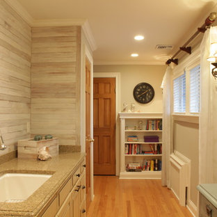 Inspiration for a large country single-wall utility room in New York with an undermount sink, raised-panel cabinets, beige cabinets, granite benchtops, grey walls, medium hardwood floors, a side-by-side washer and dryer, brown floor, grey splashback, multi-coloured benchtop and planked wall panelling.