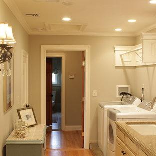 Idéer för att renovera ett stort lantligt linjärt grovkök, med en undermonterad diskho, luckor med upphöjd panel, beige skåp, granitbänkskiva, grå väggar, mellanmörkt trägolv, en tvättmaskin och torktumlare bredvid varandra, brunt golv, grått stänkskydd och stänkskydd i trä