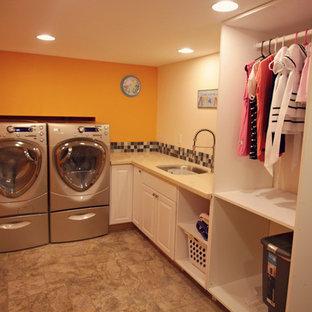 Idéer för en mellanstor modern l-formad tvättstuga enbart för tvätt, med en undermonterad diskho, luckor med upphöjd panel, vita skåp, orange väggar, en tvättmaskin och torktumlare bredvid varandra, bänkskiva i kvarts och klinkergolv i keramik