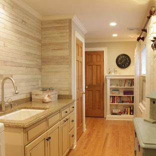 Inredning av ett lantligt stort flerfärgad linjärt flerfärgat grovkök, med en undermonterad diskho, luckor med upphöjd panel, beige skåp, granitbänkskiva, grå väggar, mellanmörkt trägolv, en tvättmaskin och torktumlare bredvid varandra, brunt golv och grått stänkskydd