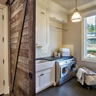 Idéer för en stor klassisk u-formad tvättstuga enbart för tvätt, med en rustik diskho, luckor med infälld panel, vita skåp, bänkskiva i kvarts, beige väggar, klinkergolv i porslin och en tvättmaskin och torktumlare bredvid varandra