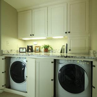 Klassisk inredning av ett linjärt grovkök, med luckor med upphöjd panel, vita skåp, heltäckningsmatta, tvättmaskin och torktumlare byggt in i ett skåp och grå väggar