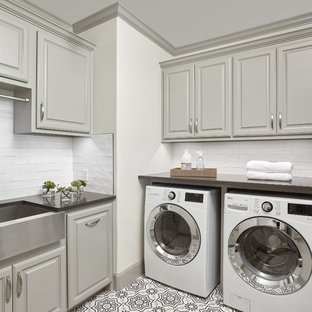 Photo of a large traditional l-shaped utility room in Dallas with a belfast sink, raised-panel cabinets, grey cabinets, white walls, a side by side washer and dryer, multi-coloured floors and grey worktops.