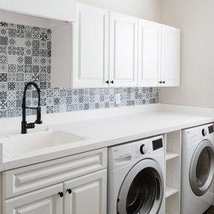 Inspiration för lantliga vitt tvättstugor, med en allbänk, vita skåp, laminatbänkskiva, stänkskydd i mosaik, beige väggar och en tvättmaskin och torktumlare bredvid varandra