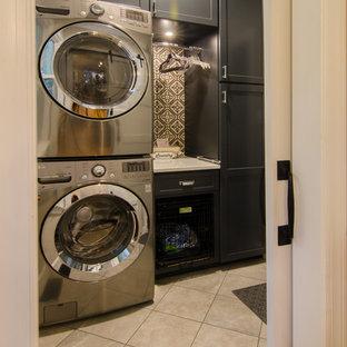 Immagine di una piccola sala lavanderia tradizionale con ante lisce, ante in legno bruno, top in quarzo composito, pavimento in gres porcellanato, lavatrice e asciugatrice a colonna, pavimento marrone e top bianco