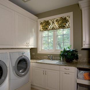 Idee per un'ampia sala lavanderia classica con lavello da incasso, ante con bugna sagomata, ante bianche, top in superficie solida, pareti verdi, pavimento in gres porcellanato e lavatrice e asciugatrice affiancate