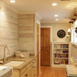 Photo of a large country single-wall utility room in New York with an undermount sink, raised-panel cabinets, beige cabinets, granite benchtops, grey walls, medium hardwood floors, a side-by-side washer and dryer, brown floor, grey splashback, timber splashback and planked wall panelling.