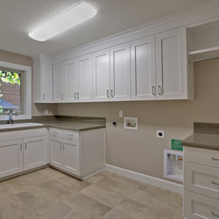 Inspiration for a large contemporary l-shaped ceramic tile dedicated laundry room remodel with a single-bowl sink, shaker cabinets, white cabinets, tile countertops, beige walls and a side-by-side washer/dryer