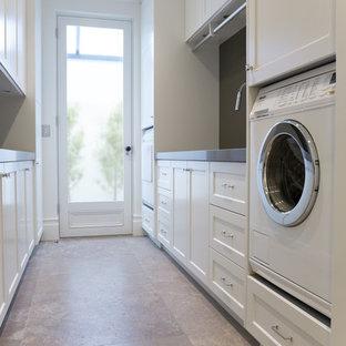 Inspiration för ett stort vintage parallellt grovkök, med en undermonterad diskho, luckor med infälld panel, vita skåp, bänkskiva i kvarts, vita väggar och travertin golv