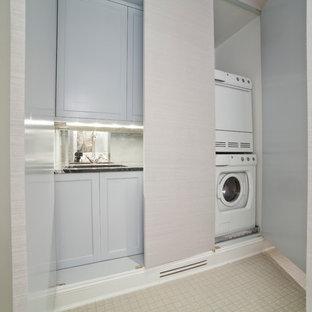 Foto på en liten funkis linjär liten tvättstuga, med en enkel diskho, luckor med infälld panel, vita skåp, granitbänkskiva, grå väggar, klinkergolv i keramik och en tvättpelare