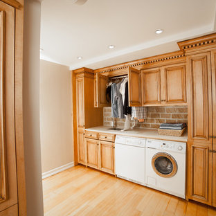 Large elegant single-wall laminate floor and yellow floor utility room photo in New York with an undermount sink, raised-panel cabinets, medium tone wood cabinets, granite countertops, blue walls, a side-by-side washer/dryer and beige countertops