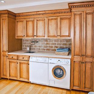 Inredning av ett klassiskt stort beige linjärt beige grovkök, med luckor med upphöjd panel, granitbänkskiva, en tvättmaskin och torktumlare bredvid varandra, en undermonterad diskho, skåp i mellenmörkt trä, blå väggar, laminatgolv och gult golv
