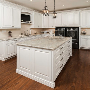 Example of a classic l-shaped dark wood floor utility room design in Other with an undermount sink, raised-panel cabinets, white cabinets, beige walls and beige countertops