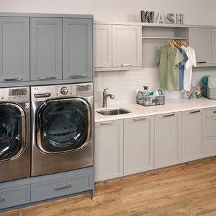 Inredning av en klassisk mellanstor linjär tvättstuga enbart för tvätt, med en undermonterad diskho, luckor med infälld panel, grå skåp, bänkskiva i koppar, grå väggar, mörkt trägolv, en tvättmaskin och torktumlare bredvid varandra och brunt golv