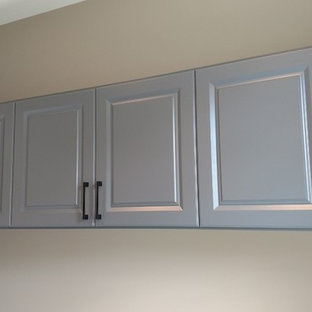 Large minimalist single-wall medium tone wood floor and brown floor utility room photo in Other with raised-panel cabinets, gray cabinets, laminate countertops and beige walls