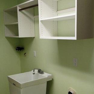 Idées déco pour une buanderie linéaire moderne dédiée et de taille moyenne avec un évier utilitaire, un placard à porte plane, des portes de placard blanches, un mur vert et des machines côte à côte.