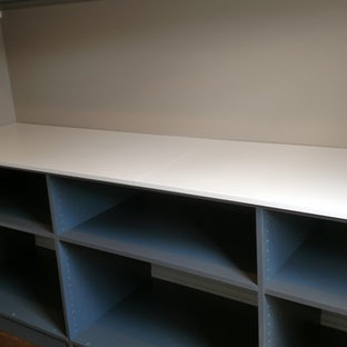 Example of a large minimalist single-wall medium tone wood floor and brown floor utility room design in Other with raised-panel cabinets, gray cabinets, laminate countertops and beige walls
