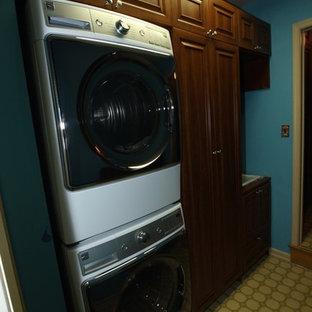 Immagine di una lavanderia multiuso chic di medie dimensioni con ante con bugna sagomata, ante in legno scuro, pareti blu e lavatrice e asciugatrice a colonna