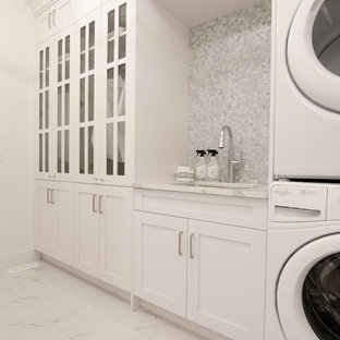 Large contemporary separated utility room in Calgary with a submerged sink, shaker cabinets, white cabinets, engineered stone countertops, white walls, porcelain flooring, a stacked washer and dryer, white floors and white worktops.
