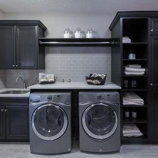 Idee per una lavanderia contemporanea con lavello sottopiano, ante con bugna sagomata, top in quarzite, pareti grigie, lavatrice e asciugatrice affiancate e ante nere