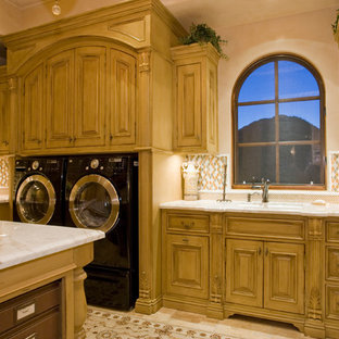 Expansive transitional u-shaped dedicated laundry room in Phoenix with flat-panel cabinets, medium wood cabinets, granite benchtops, beige walls, porcelain floors, a side-by-side washer and dryer and an undermount sink.