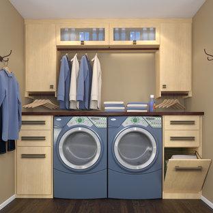 Foto på en liten funkis linjär tvättstuga, med släta luckor, skåp i ljust trä, laminatbänkskiva och en tvättmaskin och torktumlare bredvid varandra