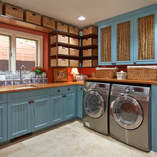 Design ideas for a large l-shaped separated utility room in Denver with blue cabinets, red walls, a submerged sink, wood worktops, porcelain flooring, a side by side washer and dryer and beige floors.