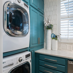 Ispirazione per una sala lavanderia classica con ante con bugna sagomata, ante turchesi, pareti bianche, lavatrice e asciugatrice a colonna e top bianco