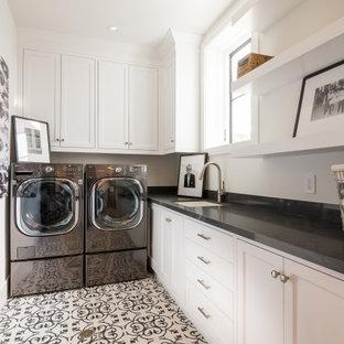 Bild på en vintage svarta l-formad svart tvättstuga enbart för tvätt, med en undermonterad diskho, luckor med infälld panel, vita skåp, en tvättmaskin och torktumlare bredvid varandra och flerfärgat golv