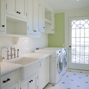 Photo of a mid-sized beach style single-wall dedicated laundry room in San Diego with a farmhouse sink, shaker cabinets, white cabinets, green walls, ceramic floors and a side-by-side washer and dryer.