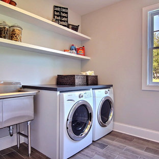 Inspiration för en mellanstor vintage tvättstuga enbart för tvätt, med en allbänk, träbänkskiva, beige väggar, klinkergolv i keramik och en tvättmaskin och torktumlare bredvid varandra