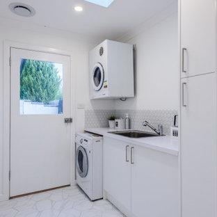 Idéer för små funkis vitt grovkök med garderob, med en enkel diskho, vita skåp, bänkskiva i kvarts, grått stänkskydd, stänkskydd i keramik, vita väggar, laminatgolv och flerfärgat golv