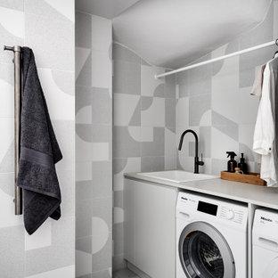 Idee per una piccola lavanderia multiuso scandinava con lavello da incasso, top in quarzo composito, pareti grigie, pavimento in gres porcellanato, lavatrice e asciugatrice affiancate, pavimento grigio e top bianco