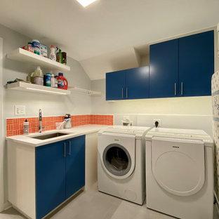 Immagine di una lavanderia multiuso minimal di medie dimensioni con lavatoio, ante lisce, ante blu, top in laminato, paraspruzzi arancione, paraspruzzi con piastrelle in ceramica, pareti bianche, pavimento in gres porcellanato, lavatrice e asciugatrice affiancate, pavimento grigio e top bianco