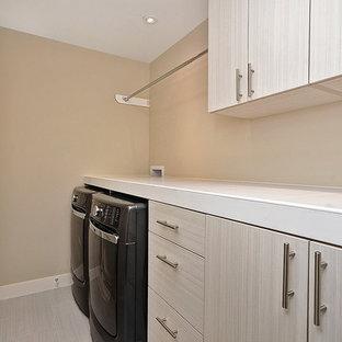 Inredning av en modern liten vita linjär vitt tvättstuga enbart för tvätt, med släta luckor, skåp i ljust trä, kaklad bänkskiva, beige väggar, laminatgolv, en tvättmaskin och torktumlare bredvid varandra och beiget golv