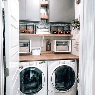 Inspiration for a small single-wall laundry cupboard in Houston with grey cabinets, wood benchtops, beige walls, ceramic floors, a side-by-side washer and dryer, white floor, brown benchtop and wood.
