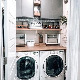 Idéer för att renovera en liten bruna linjär brunt liten tvättstuga, med grå skåp, träbänkskiva, beige väggar, klinkergolv i keramik, en tvättmaskin och torktumlare bredvid varandra och vitt golv