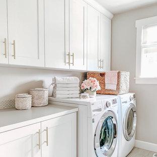 Exempel på en mellanstor klassisk vita parallell vitt tvättstuga enbart för tvätt, med vita skåp, en tvättmaskin och torktumlare bredvid varandra, grått golv, bänkskiva i kvartsit, vitt stänkskydd, stänkskydd i keramik, beige väggar och klinkergolv i keramik