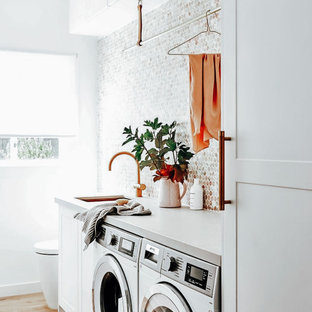 Inspiration for a mid-sized single-wall medium tone wood floor and brown floor dedicated laundry room remodel in Dallas with an undermount sink, white cabinets, quartzite countertops, gray backsplash, mosaic tile backsplash, white walls, a side-by-side washer/dryer and gray countertops